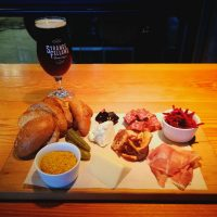 Photo shows a charcuterie board with bread, meats, cheese, mustard in a ramekin, shredded beets in a ramekin, and a dark beer in a tulip glass.